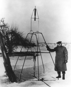Robert Goddard, rocket, and launching frame at his Aunt's farm in Auburn, MA (1926).